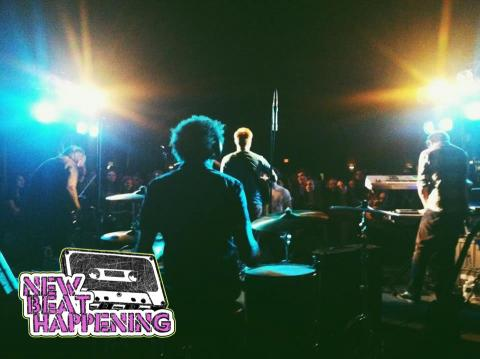 New Beat Happening logo in corner of image of band performing.