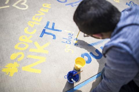 Student Organization Resource Center student employee painting the cement outside of the Michigan Union