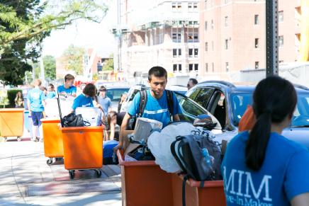 Student helping another student move in their possessions.