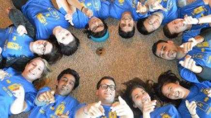 Image of LeaderShape participants and facilitators lying on the floor in a circle looking up toward the camera and smiling.