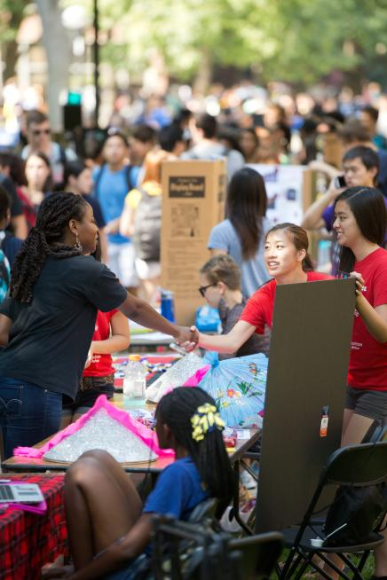 students shake hands across a table at Festifall