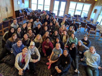 Image is of 2019 Leadership Connection participants sitting on the floor at Camp Michigania and smiling at the camera.